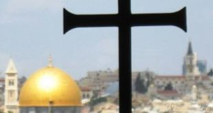 In Israel, a Christian cross is pictured in the foreground with a Muslim mosque in the background. (Wikimedia Commons Photo)